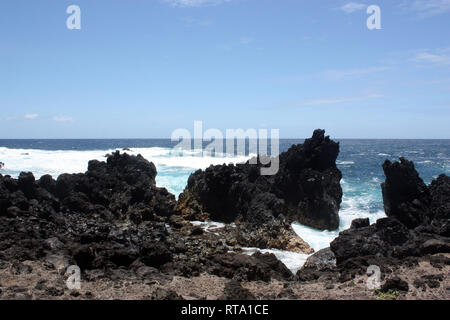 Large, jagged, black lava rock and boulders fronting the Pacific Ocean at Laupahoehoe Point in Hawaii, USA - Stock Photo