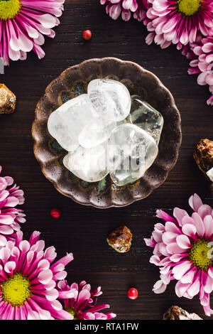 Clear Quartz Crystals with Garnet and Pink Mums on Dark Wood - Stock Photo