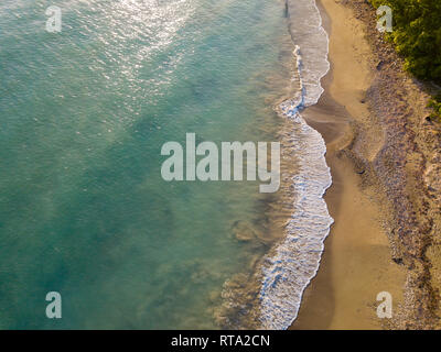 Aerial Drone shot showing the wave breaks on the  golden coloured sand beach - Stock Photo