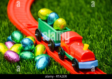 Pile of Easter Eggs waiting to be transported by toy train on tracks on lawn.  Colourful childhood play, travel concept for Easter with Easter Eggs. - Stock Photo