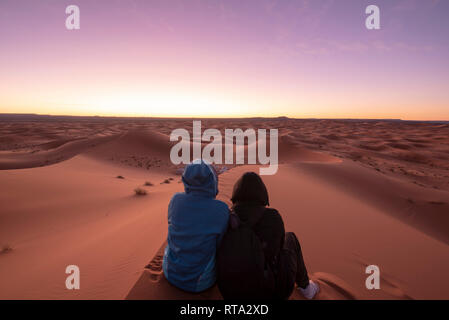 People are watching the Amazing sunrise over the dunes Erg Chebbi in the Sahara desert . Beautiful sand landscape with stunning sky. Merzouga, Morocco - Stock Photo