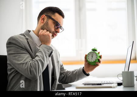 Young businessman is working in office. He is running late on schedule. - Stock Photo