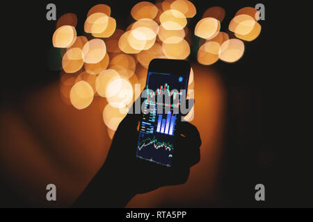 Silhouette of female hand holding smart phone in the dark with stock trading on display with light bokeh blurred background, Mobile business concept - Stock Photo
