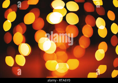 A group of circle and oval shape from red and yellow lights defocused abstract background, Lens aperture bokeh blurred effect - Stock Photo