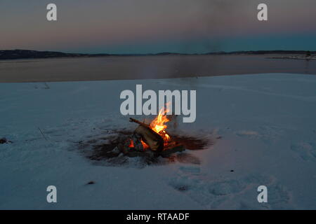 A camp fire is burning at the shore of a bay of the Baltic Sea. It's sunset on a winter day and the beach is covered in snow. - Stock Photo