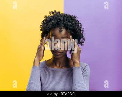Woman having headache. Isolated on gray background. Businesswoman standing with stress isolated on trendy studio color background. Female half-length portrait. Human emotions, facial expression concept. - Stock Photo