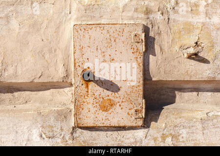 Rusty metal door of the electric box. Old abandoned electrical junction box on the wall of an old house. - Stock Photo