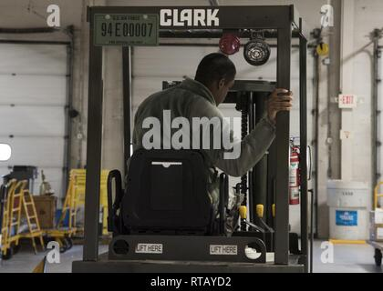 Airman Anthony Lemarc Cole Jr., a traffic management specialist, 108th Logistics Readiness Squadron, parks a forklift in the LRS supply warehouse at Joint Base McGuire-Dix-Lakehurst, N.J., Feb. 4, 2019. In his year and two months of service, Cole said his proudest moment so far was passing his career development course test and becoming a temporary technician within his shop. - Stock Photo