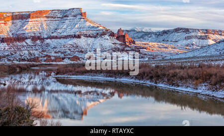 Snow from a recent storm  line the banks of the Colorado and the mesas and mountains surrounding Fisher Towers near Moab, Utah. - Stock Photo