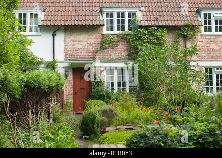 Traditional style English front garden in rural Kent in summer with house, red door and climbers, near the AONB High Weald area. Seen while hiking. - Stock Photo
