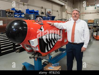 John Hutton, principal technical manager, Littoral and Mine Warfare Systems  at Naval Surface Warfare Center Panama City Division poses with an unmanned  underwater vehicle used for mine countermeasure testing. - Stock Photo
