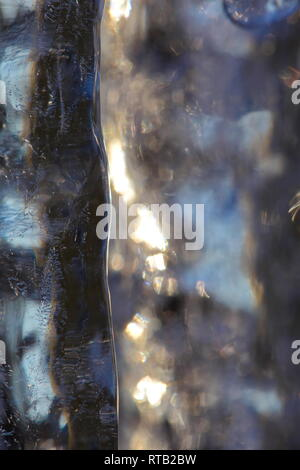 Close up of a row of icicles glittering in the light of the golden winter sun. - Stock Photo