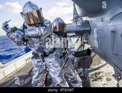 PACIFIC OCEAN (Feb. 6, 2019) Aviation Boatswain's Mate (Handling) 3rd Class Frederick Medina, left, from Delano, California, and Aviation Boatswain's Mate (Handling) Airman Eddie De La Cruz, from Garden Grove, California, prepare to extinguish a simulated hot spot during a flight deck fire drill aboard the San Antonio-class amphibious transport dock ship USS Anchorage (LPD 23) while on a deployment of the Essex Amphibious Ready Group (ARG) and 13th Marine Expeditionary Unit (MEU). The Essex ARG/13th MEU is a capable and lethal Navy-Marine Corps team deployed to the 7th fleet area of operations - Stock Photo