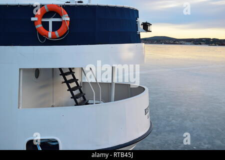 Detail on a metal ship lying moored in an ice covered harbor bay: a ladder is leading to the upper deck. - Stock Photo