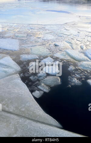 Ice covering a harbor bay in winter is shimmering in the light of the setting sun. - Stock Photo