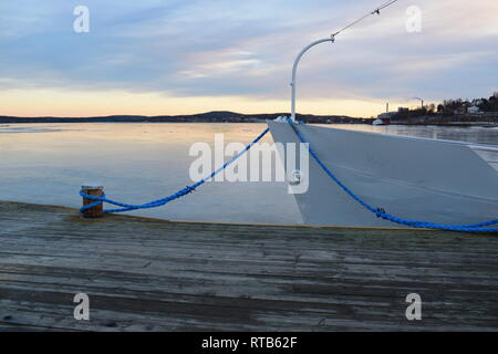 A ship lies moored in an ice covered harbor bay. - Stock Photo