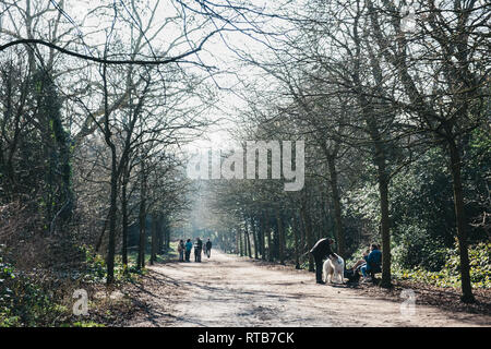 London, UK - February 23, 2019: People walking inside Holland Park, London, on the hottest spring day. Holland park is the largest park in Kensington  - Stock Photo
