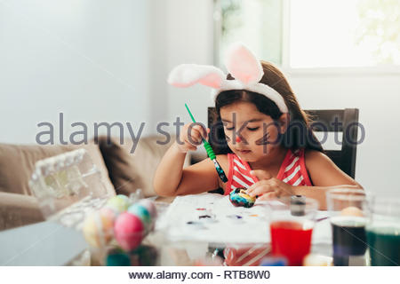Happy easter! A beautiful child girl painting Easter eggs. Happy family preparing for Easter. Cute little child girl wearing bunny ears on Easter day - Stock Photo