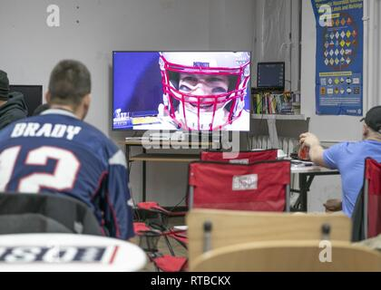 ZAGAN, Poland (Feb. 3, 2019) – U.S. service members supporting the 1st Armored Brigade Combat Team, 1st Infantry Division, watch as the New England Patriots face off against the Los Angeles Rams in Super Bowl 53. SMs donning their favorite sports jerseys, gather around televisions in the USO and dining facility to cheer on their favorite team as Super Bowl 53 kicked off in Atlanta, Georgia. - Stock Photo