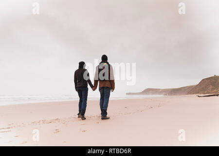 Back view of young couple with backpack in warm wear holding each other hands on sand beach near sea and hills