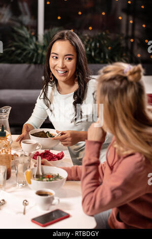 While dining in restaurant two girls sharing secrets with each other. - Stock Photo