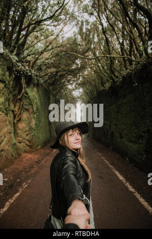 Side view of elegant lady in hat and leather jacket holding hand of person and standing on footpath between murk alley of high walls and woods - Stock Photo
