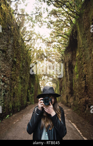 Elegant lady in hat and leather jacket shooting on camera and standing on footpath between murk alley of high walls and woods - Stock Photo
