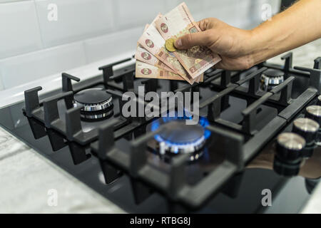 Cooktop with burning gas ring with hands holding money uah hryvnas for combustion . - Stock Photo