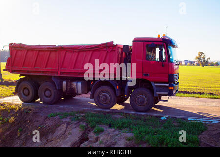 A red dump truck for sand delivery is parked with field and sky in the background - Stock Photo