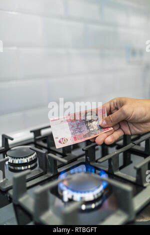 Cooktop with burning gas ring with hands holding money uah hryvnas for combustion at home. - Stock Photo
