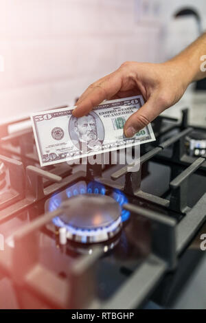 Cooktop with burning gas ring with hands holding money 50 dollars for combustion - Stock Photo
