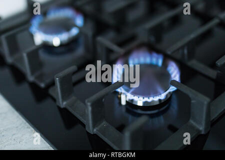 Cooktop with burning gas ring. Gas cooker with blue flames. Tinted photo. - Stock Photo