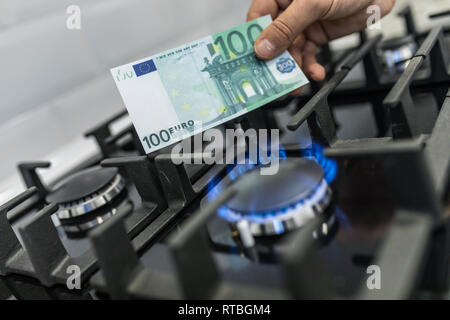 Cooktop with burning gas ring with hands holding money 100 euro for combustion - Stock Photo