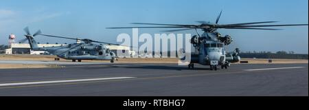 Two U.S. Marine Corps CH-53E Super Stallions prepare for take-off at Marine Corps Air Station New River, North Carolina, Feb. 8, 2019. Marine Heavy Helicopter Squadron (HMH) 464 is participating in a cold weather training exercise in Brunswick, Maine. Executing this training ensures that HMH-464 is prepared to support the Marine Air-Ground Task Force (MAGTF) commander during all phases of expeditionary operations. The aircraft are assigned to HMH-464, Marine Aircraft Group 29, 2nd Marine Aircraft Wing. - Stock Photo