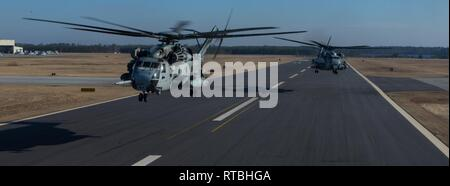 Two U.S. Marine Corps CH-53E Super Stallions take-off at Marine Corps Air Station New River, North Carolina, Feb. 8, 2019. Marine Heavy Helicopter Squadron (HMH) 464 is participating in a cold weather training exercise in Brunswick, Maine. Executing this training ensures that HMH-464 is prepared to support the Marine Air-Ground Task Force (MAGTF) commander during all phases of expeditionary operations. The aircraft are assigned to HMH-464, Marine Aircraft Group 29, 2nd Marine Aircraft Wing. - Stock Photo