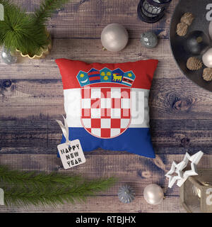 Happy New Year tag with Croatia flag on pillow. Christmas decoration concept on wooden table with lovely objects. - Stock Photo