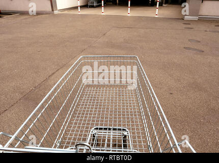 Man hand POV over the supermarket cart in front of the entrance with modern food mall supermarket  - Stock Photo
