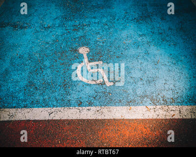 Disabled sign seen on the asphalt with blue marked special parking area - Stock Photo