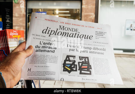 PARIS, FRANCE - SEP 25, 2017: Man buying latest Mode Diplomatique newspaper with titles Donald Trump overwhelmed by anti-Russian party and hell of the German miracle - Stock Photo