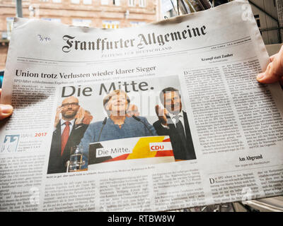 PARIS, FRANCE - SEP 25, 2017: Man buying latest frankfurter allgemeine german newspaper with portrait of Angela Merkel after election in Germany for the Chancellor of Germany, the head of the federal government - Stock Photo