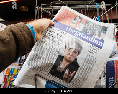 PARIS, FRANCE - SEP 25, 2017: Man buying latest The Guardian newspaper from press kiosk with Braking news from Theresa May British Prime Minister 'Brexit delayed two years' - Stock Photo