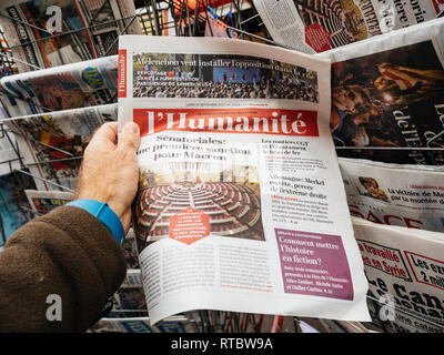 PARIS, FRANCE - SEP 25, 2017: Man buying latest  newspaper with portrait of Angela Merkel after election in Germany for the Chancellor of Germany, the head of the federal government - Stock Photo
