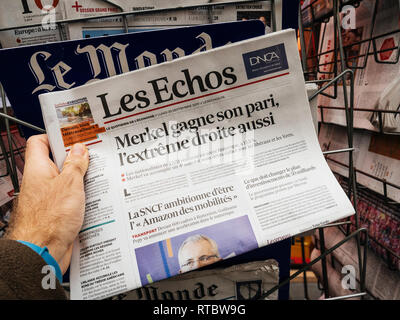 PARIS, FRANCE - SEP 25, 2017: Man buying latest  Les Echos newspaper with news about Angela Merkel winner after election in Germany for the Chancellor of Germany, the head of the federal government - Stock Photo
