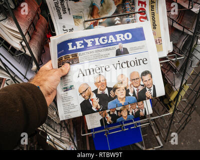 PARIS, FRANCE - SEP 25, 2017: Man buying latest Le Figaro with Bitter Vitory message about Angela Merkel winning election in Germany for the Chancellor of Germany, the head of the federal government - Stock Photo