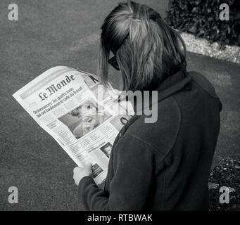 PARIS, FRANCE - SEP 24, 2017: View from above of woman reading latest newspaper Le Monde with portrait of Angela Merkel before the election in Germany for the Chancellor of Germany, the head of the federal government - Stock Photo