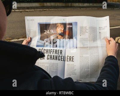 PARIS, FRANCE - SEP 24, 2017: Side view of woman reading latest newspaper Le Monde with article investigation about Angela Merkel before the election in Germany for the Chancellor of Germany, the head of the federal government - Stock Photo
