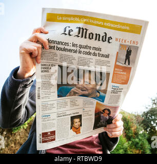 PARIS, FRANCE - SEP 24, 2017: View from below of woman reading latest newspaper Le Monde with portrait of Angela Merkel before the election in Germany for the Chancellor of Germany, the head of the federal government - Stock Photo
