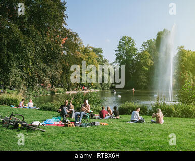 STRASBOURG, FRANCE - SEP 24, 2017: Crowd of people enjoying the sun on an early autumn day in Strasbourg Orangerie public park on the border of a lake with a fountain  - Stock Photo