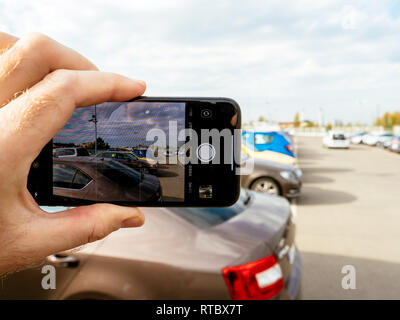 FRANKFURT, GERMANY - NOV 4, 2017: Man taking pictures with the new Apple iPhone X of a rooftop parking - pov  - Stock Photo