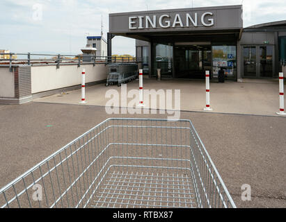 FRANKFURT, GERMANY - NOV 4, 2017: Man hand POV over the supermarket cart in front of the entrance with Eingang sign to the Edeka store - Stock Photo